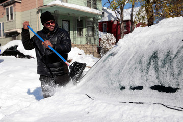 Charles Stevens cleans the snow off his vehicle in Detroit, Michigan,