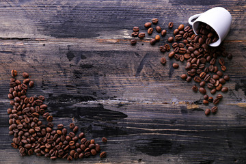 Coffee cup with roasted brown beans scattered on wood textured table with a lot copy space for text. Flat lay composition. Close up, top view, background.