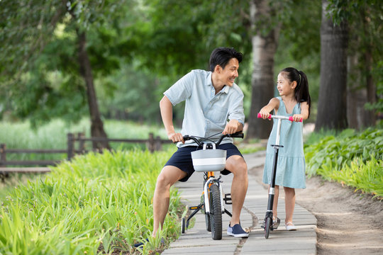 Happy Chinese father and daughter playing in park