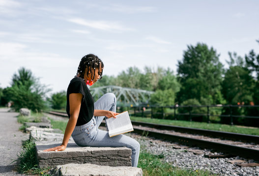 Black african young woman reading a book outdoor