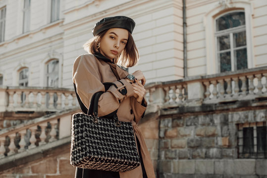 Outdoor autumn fashion portrait of young elegant woman wearing classic beige trench coat, trendy faux leather beret, holding black tweed bag, handbag, posing in street of city. Copy, empty space
