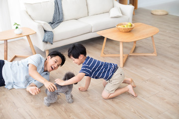 Chinese father and son playing with dog on floor