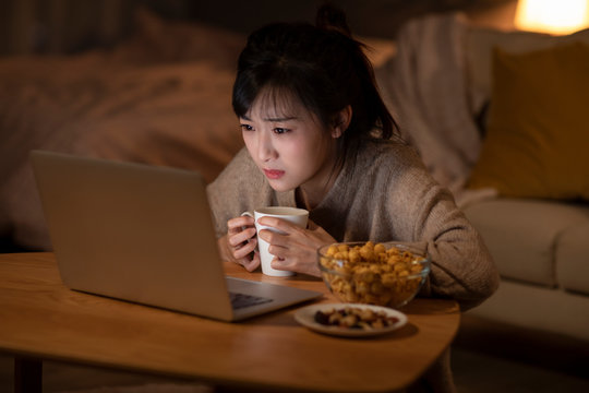 Young Chinese woman watching movie on laptop