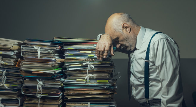 Stressed business executive overloaded with paperwork