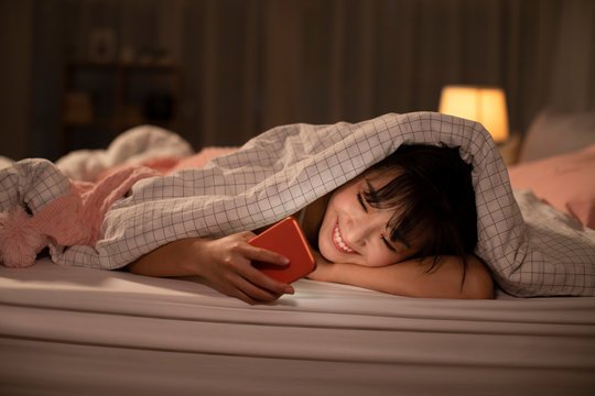 Young Chinese woman using smartphone on bed at night