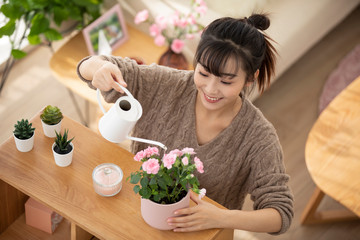 Young Chinese woman watering flowers at home