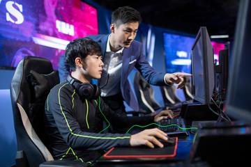 Young Chinese man coaching gamer playing esports