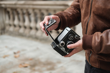 Unrecognizable tourist changing film in retro photo camera while standing on street of London