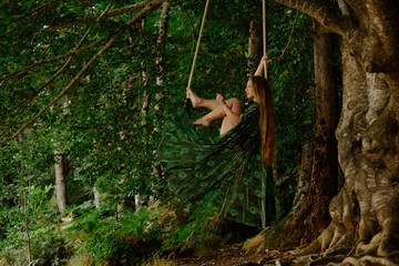 Affectionate topless woman swinging at trapeze in forest