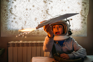 Fantasizing boy in astronaut helmet playing with paper plane at home