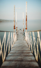 Foto op Plexiglas Stad aan het water Narrow pier with weathered railings and distant traveler located near tranquil sea water against cloudless sky