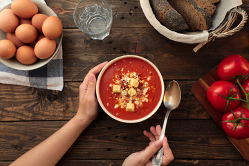 From above shot of unrecognizable person holding a bowl of red gazpacho in a rustic table with egg, bread, and fresh tomatoes arrangements