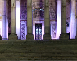 the stairs and entrance of the historic 19th century leeds city hall building illuminated at night