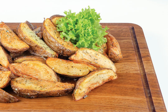 fried potato wedges. home made in rural style and served on on wooden board. healthy organic vegetarian food or beer snack. close up view