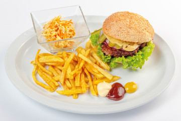 fast food menu. hamburger, french fries and salad. burger with beef stake, cheese onion and pickle. mayonnaise ketchup mustard on the white plate. healthy variation of junk food