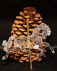 A carousel horse Christmas decoration resting against a large pine cone