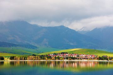 village on the shore of a lake. beautiful rural landscape in mountains. distant snow covered peaks in clouds. amazing scenery of western High Tatras in springtime