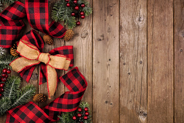 Christmas side border with red and black checked buffalo plaid ribbon, burlap and tree branches. Overhead view on a rustic wood background.