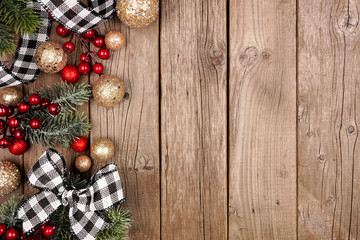 Wall Mural - Christmas side border with white and black checked buffalo plaid ribbon, decorations and tree branches. Overhead view on a rustic wood background.