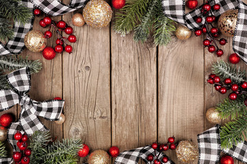 Wall Mural - Christmas frame with white and black checked buffalo plaid ribbon, baubles and tree branches. Top view on a rustic wood background.