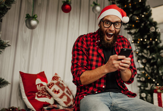 Happy man with beard in santa claus hat writting a christmas letter to santa claus from a smartphone.