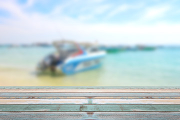 Wood table top with blurred boat at the beach