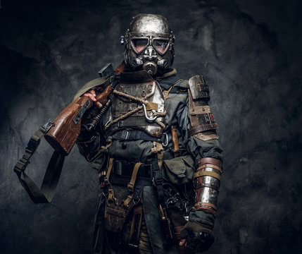 Portrait of a man in interesting costume of dark apocalypse warrior at photo studio.