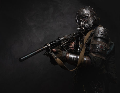 Man is wearing great costume of futuristic knight in gas mask and is holding weapon.