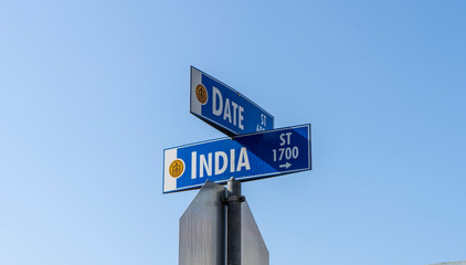 Date and India street sign with blue sky background