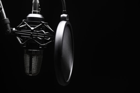 Studio microphone with pop filter with dramatic light. Concept. Leading radio, bloggers, singers, track recording, voice acting.