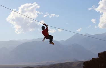 Zipline: man hanging on a rope-way, an exciting adventure