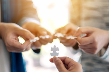 Closeup image of many people holding and putting a piece of white jigsaw puzzle together