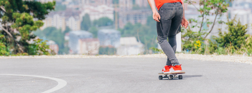Tall athlete riding his longboard fast and steady downhill while wearing red t-shirt and black jeans.