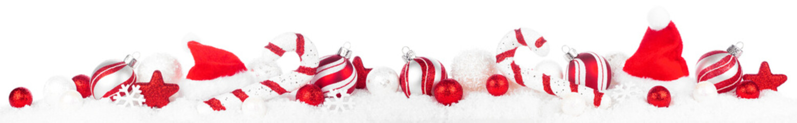 Christmas border of red and white decorations in snow. Side view isolated on a white background.
