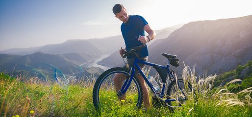 Perspective of a fit mountain biker pushing his bike uphill with amazing view on a forest, river and mountains in the background. Amazing green nature at sunset. Fototapete
