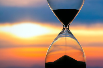 Hourglass on the background of a sunset. The value of time in life. An eternity..