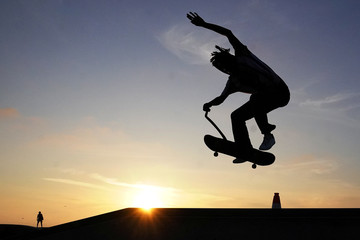 A man rides his skateboard at sunset while doing a trick in Venice Skate Park in the Venice Beach area of Los Angeles