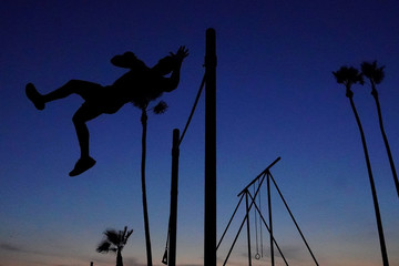 A man works in his high bar skills at sunset in the Venice Beach area of Los Angeles