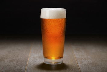 Double India pale ale beer served in a chilled pint glass on wooden counter at a craft beer pub, black background
