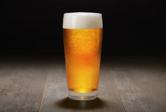 A fresh pint of India Pale ale IPA craft beer served in a cold pint glass at a brewery, black background
