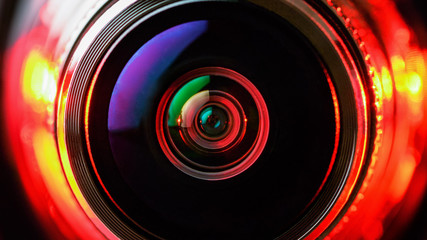 The camera lens and the beautiful light red color. Horizontal photo