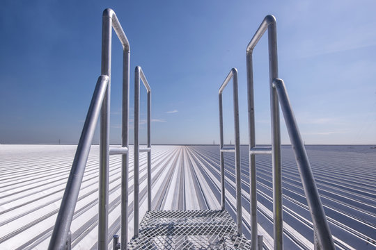 Perspective of Iron hand rail over the roof of metal sheet for industrial building and construction under the sky