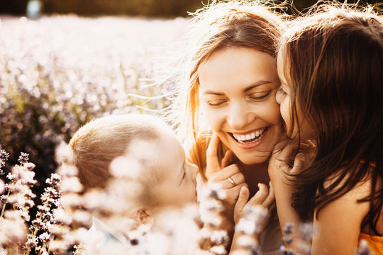 Beautiful young mother laughing while her kids are embracing and kissing her outside in a field of flowers against sunset.
