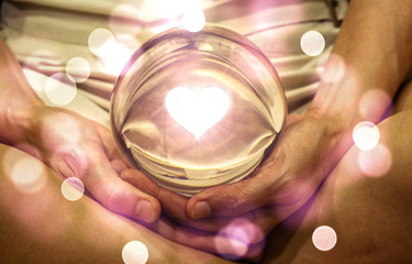 Spiritual background: Fortune teller concept, meditation hand with shining heart shape in magic glass ball,sign of love and peaceful