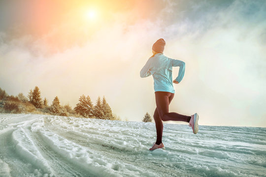 Running woman. Runner on the snow in winter sunny day. Female fi