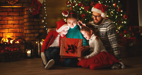 Merry Christmas! happy family mother father and children with magic gift near tree   at home.