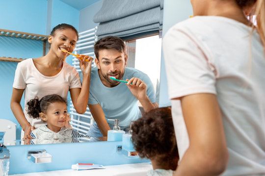 Mixed Race Family. Mother father and daughter at bathroom brushing teeth looking at mirror smiling playful