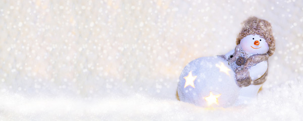 Picture for web banner. Toy snowman in a knitted hat, with a luminous ball close up on a white background. New Year and Christmas background for greetings, banner, postcard, advertisement, Copy space,