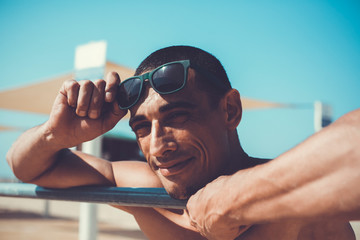 young muscular man resting and posing on the beach. Wearing sunglasses