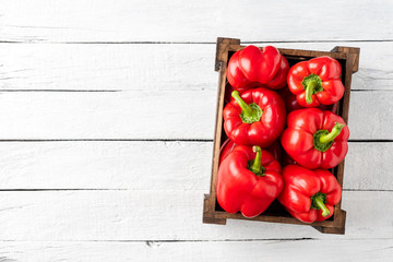 Overhead shot of red bell pepper in box on white wooden table with copyspace. Sweet paprika